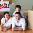 Family in their new house lying on floor with boxes — Stock Photo #10826512