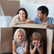 Stock Photo: Happy family playing at home with boxes