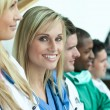 Stock Photo: Portrait of female doctor smiling at the camera with her team in a line on stairs
