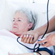 Stock Photo: Sick senior womlying on hospital bed