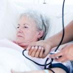 Sick senior woman lying on a hospital bed — Stock Photo