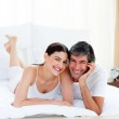 Romantic couple embracing lying on their bed — Stock Photo