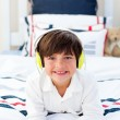 Smiling little boy listening music with headphones on - Stock Photo