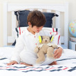 Stock Photo: Cute little boy playing with a teddy bear