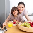 Happy mother and her child having breakfast — Stock Photo #10826796
