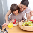 Jolly mother and her child having breakfast - Stock Photo
