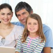 Little girl using a laptop with her parents — Stock Photo
