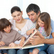 Stock Photo: Attentive parents reading with their children