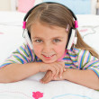 Stock Photo: Smiling little gril listening to music
