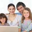 Happy family using a laptop on the sofa — Stock Photo
