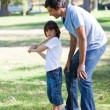 Happy father teaching baseball to his son - Stock Photo
