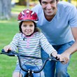 Cute little girl learning to ride a bike with her father - Foto Stock