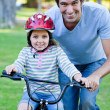 Cute little girl learning to ride a bike with her father - Zdjęcie stockowe
