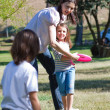 Happy mother playing frisbee with her children — Stock Photo