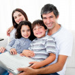 Jolly family using a laptop sitting on sofa — Stock Photo