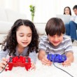 Cute siblings playing video games laying down on the floor - Stock Photo