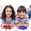 Smiling siblings playing video games lying on the floor - Foto Stock