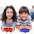 Smiling siblings playing video games lying on the floor - Stockfoto