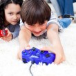 Jolly children playing video games lying on the floor - Foto Stock