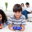 Adorable siblings playing video games lying on the floor - Foto Stock