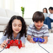 Jolly siblings playing video games lying on the floor — Stock Photo #10826956