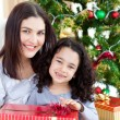 Royalty-Free Stock Photo: Mother and daughter at home holding a Christmas gift
