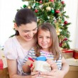 Mother and daughter playing with Christmas gifts — Stockfoto
