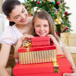 Mother and daughter at home holding a Christmas gift — Stock Photo #10827002