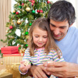 Dad and little girl playing with Christmas presents - Stock Photo