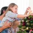 Little girl placing star in Christmas tree — Stock Photo #10827036