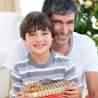 Father and son holding a Christmas gift — Stock Photo #10827047