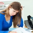 Stock Photo: Stressed student doing her homework on desk