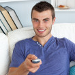 Smiling man relaxing in the living-room watching television — Stock Photo