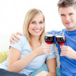 Cute couple drinking wine together in the living-room — Stockfoto