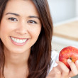 Smiling young woman holding a red an apple — Stock Photo