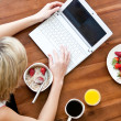 Blond woman using a laptop while having breakfast at home — Stock Photo #10827206