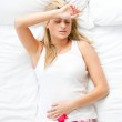 Upset woman having a migraine lying on a bed at home — Stock Photo #10827213