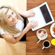 Stock Photo: Pretty woman using a laptop while having breakfast at home