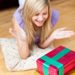 Stock Photo: Surprised young woman opening gifts lying on the floor in the living-room
