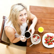 Stock Photo: Pretty woman having an healthy breakfast in a living-room