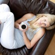 Charming woman drinking coffee sitting on a sofa in a living-room — Stock Photo #10827260