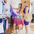 Stock Photo: Bright women choosing clothes together