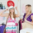 Smiling women choosing clothes together — Stock Photo