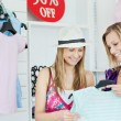 Cute young women choosing clothes together — Stock Photo