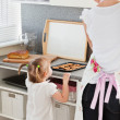 Small girl taking a cookie in kitchen — Stock Photo