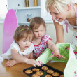 Mother baking cookies for her two girls — Stock Photo