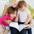 Cute mother reading a book with children — Stock Photo