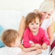 Smiling woman working with her children at laptop — Stock Photo #10827844