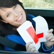 Cheerful young female driver tearing up her L sign — Stock Photo #10828484