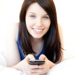 Happy young woman texting while lying on a bed — Stock Photo